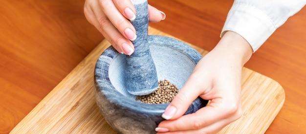 Handen van vrouwen malende peper in mortier