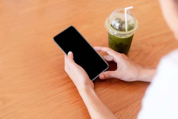 Handen van vrouwen met lege leeg scherm smartphone in café.