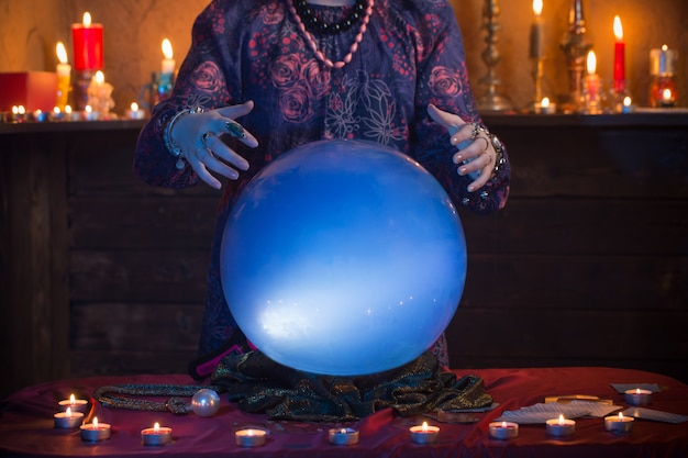 Handen van waarzegster met verlichte kristallen bol