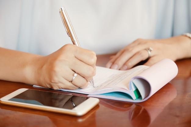 Handen van zakelijke dame schrijven plannen en ideeën in kladblok