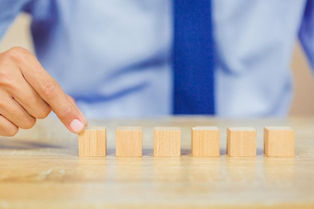 Handen van zakenlieden, die houten blokken stapelen.
