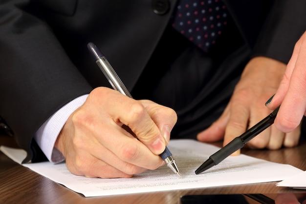 Handen van zakenlieden en vrouwen die de documenten bestuderen