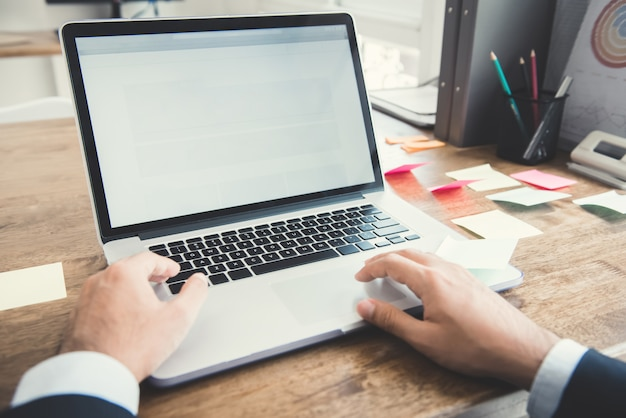 Handen van zakenman die notitieboekjecomputer met behulp van bij werkend bureau in het bureau