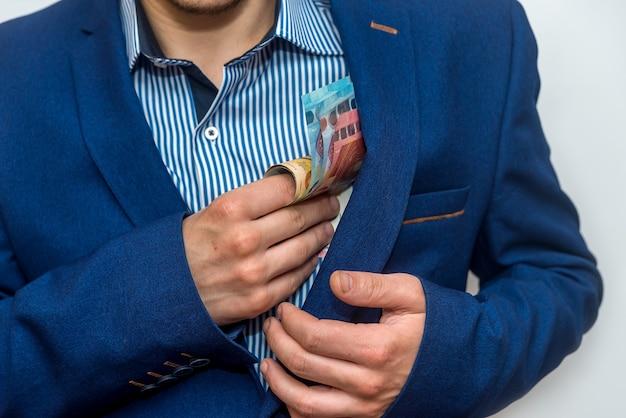 Handen van zakenman euro verbergen in zak
