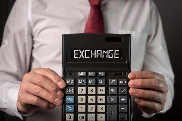 Handen van zakenman met uitwisselingswoord op calculator.
