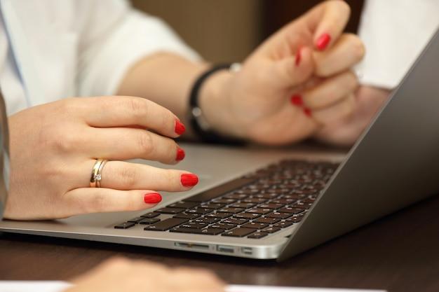 Handen van zakenvrouw die op laptop werkt