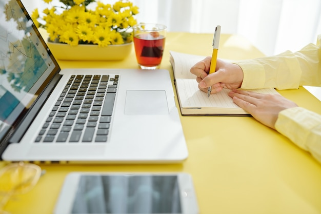 Handen van zakenvrouw rapport van scherm van laptop analyseren en notities maken in planner