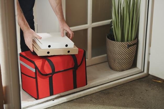 Handen van zieke jongeman die twee dozen met bezorgde pizza en grote rode zak met voedselproducten bij de deur neemt terwijl hij thuis blijft