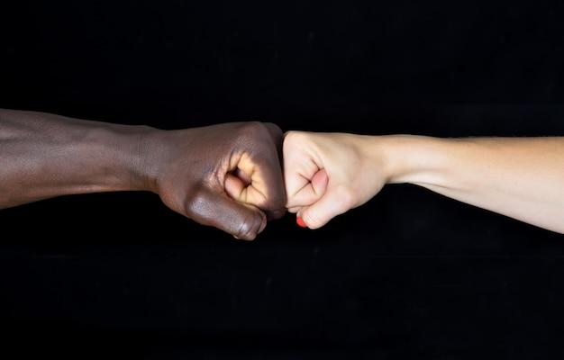 Handen van zwarte man en witte vrouw op zwarte achtergrond