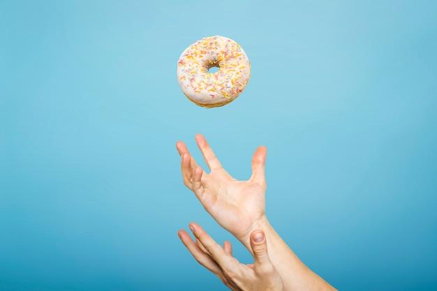 Handen vangen een donut met suikerglazuur. concept van het bakken, handgemaakt. plat lag, bovenaanzicht