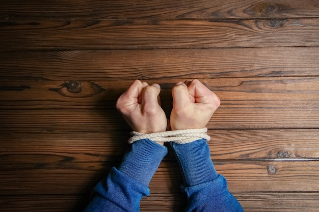 Handen vastgebonden met een touw levensbedreigend op een houten achtergrond.