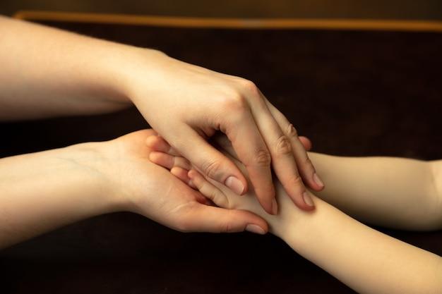 Handen vasthouden, klappen als vrienden. close-up shot van vrouw en kind handen doen verschillende dingen samen. familie, huis, onderwijs, jeugd, liefdadigheidsconcept. moeder en zoon of dochter, rijkdom.
