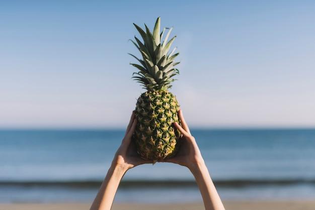 Handen verhogen ananas op het strand
