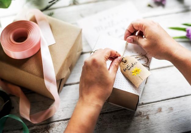 Handen verpakking huidige doos met bloem decoratie handwerk