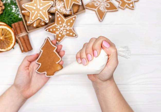 Handen versieren handgemaakte kerstkoekjes met glazuur