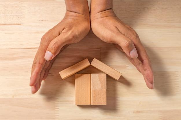 Handen voor houten huis
