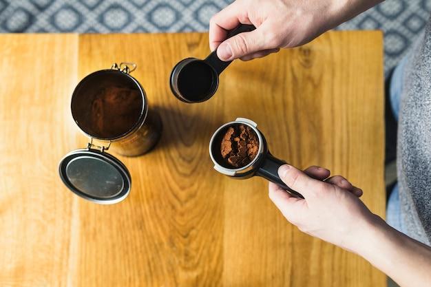 Handen vullen filter met koffie poeder