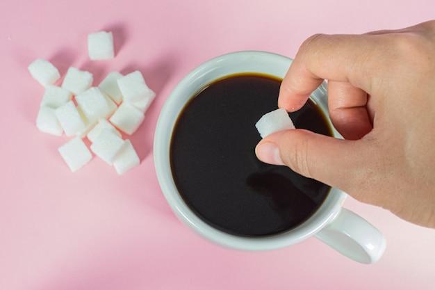Handen vullen suikerklontjes in koffie op roze.