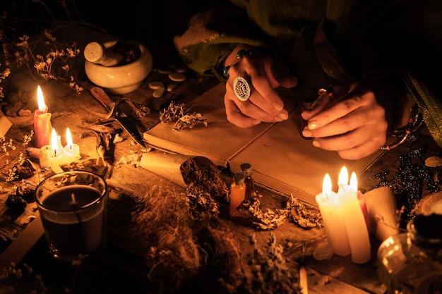 Handen waarzegster over een oude tafel met kruiden en boeken. manifestatie van occultisme in de vorm van waarzeggerij.