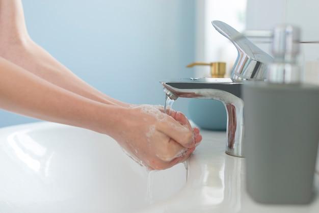Handen wassen in de gootsteen met water en zeep
