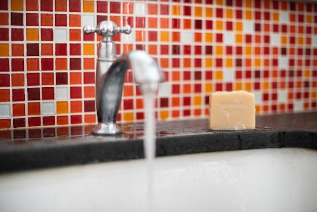 Handen wassen met open kraan en stuk zeep