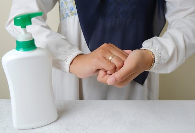 Handen wassen met vloeibare zeep of alcoholgel van pompfleshygiëne en gezondheidszorgconcept