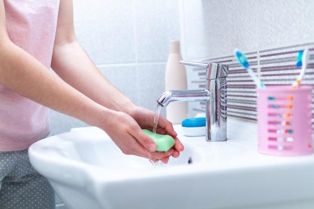Handen wassen met zeep onder de kraan met water in de badkamer. hygiëne concept en handverzorging. bescherming en preventie tegen virussen en bacteriën