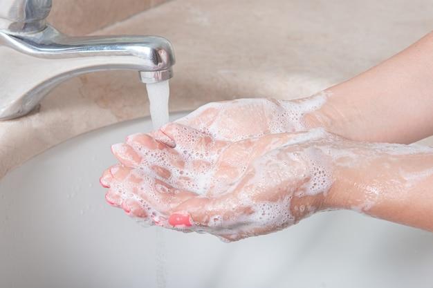 Handen wassen met zeep onder de kraan