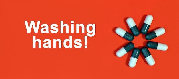 Handen wassen - witte tekst op een rode achtergrond met pillencapsules
