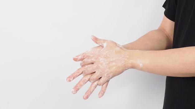 Handen wassen wrijven met zeep schuim veeg voor preventie en hygiëne met aziatische man draagt een zwart t-shirt