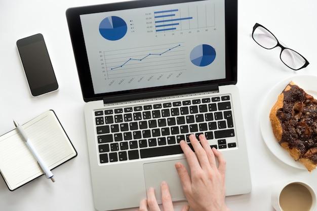 Handen werken op een laptop met een diagram erop