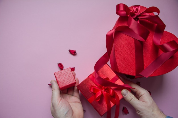 Handen wikkelen rode geschenkdoos hartvorm met rood lint
