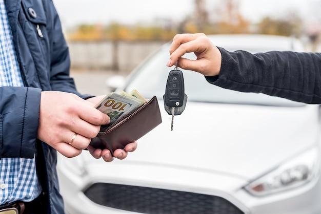 Handen wisselen met autosleutels en eurobankbiljetten