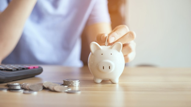 Handen zetten geldmunt in spaarvarken om geldrijkdom te besparen