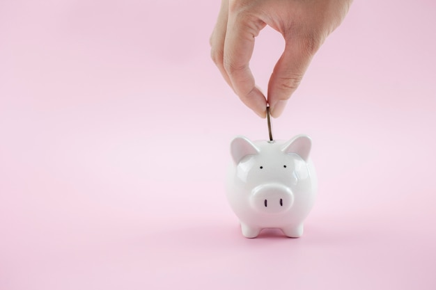 Handen zetten geldmunt in spaarvarken op roze achtergrond om geldrijkdom te besparen
