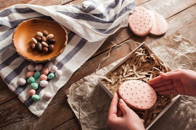 Handen zetten koekje in doos met houten krullen.