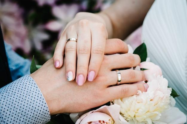 Handen zijn jonggehuwden met trouwringen