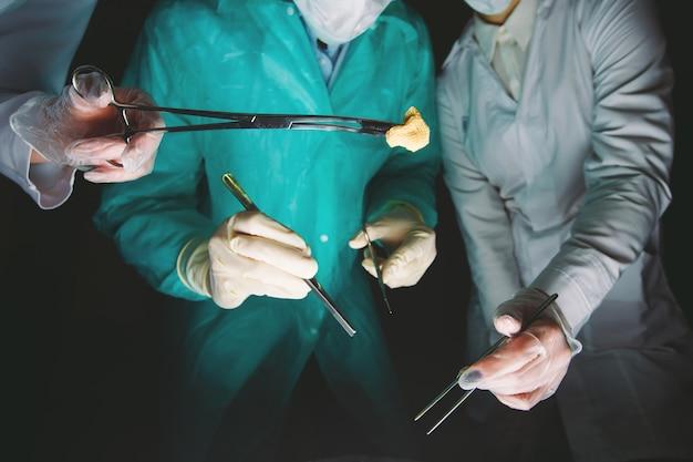 Handenclose-up van chirurgen die medische instrumenten houden. de chirurg maakt een operatie.