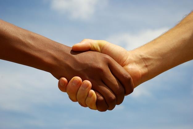Handenhandenschudden en grijze hemel