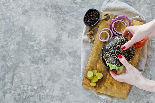 Handenmeisjes houden zwarte hamburger. boven bekijk copyspace