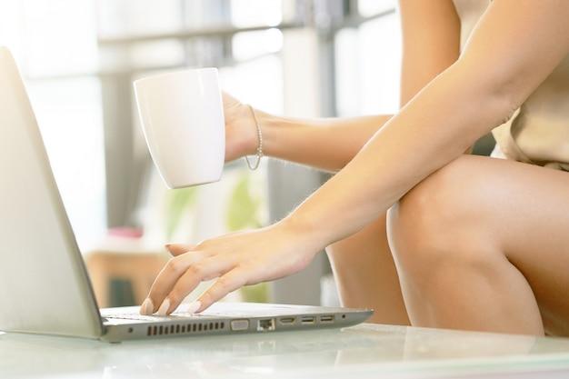 Handenvrouw met laptop, die thuis in toevallige atmosfeer werken. vrouwenhanden gebruikt haar laptop en houdt een witte koffiekop.