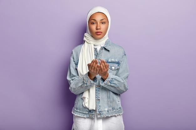 Handgebaar en biddende concept. ernstige vrouw met donkere huid steekt handen in gebed, pleit voor iets, draagt sjaal en spijkerjasje, geïsoleerd over paarse muur. moslim religie concept