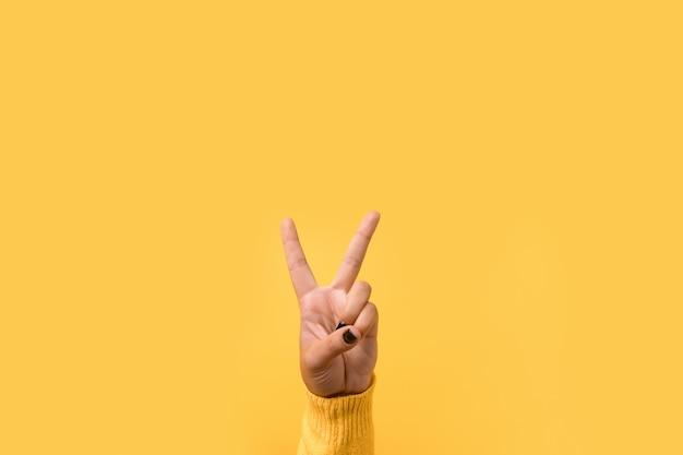 Handgebaar v-teken over gele ruimte