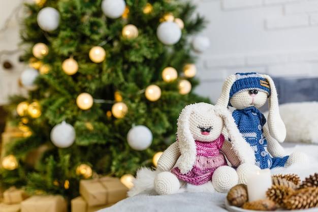 Handgemaakt gebreid konijn. kerstkonijntje in een sjaal en muts met een grote pumpon tussen de decoratieve kerstbomen en ballen. kerst samenstelling