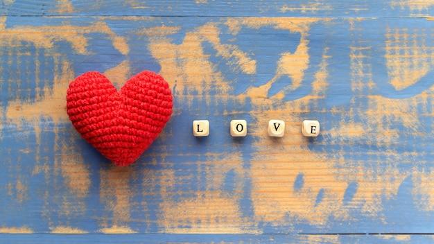 Handgemaakt gebreid rood hart met houten letters die woordliefde samenstellen. bovenaanzicht