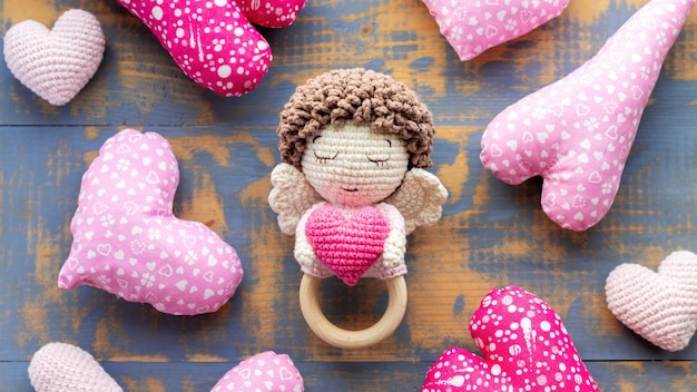Handgemaakt gebreid speelgoed voor kinderen en een roze hartje. bovenaanzicht
