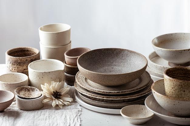 Handgemaakt keramisch vaatwerk, lege ambachtelijke ceramische platen, kommen en kopjes op lichte achtergrond