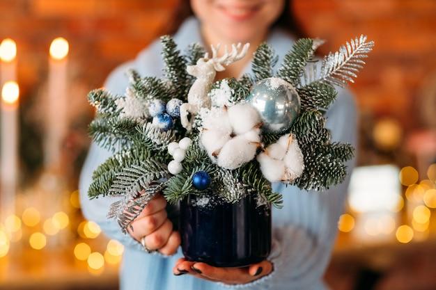 Handgemaakt kerstcadeau. dame met decoratief arrangement, pot met dennenboomtakjes en katoenplant.