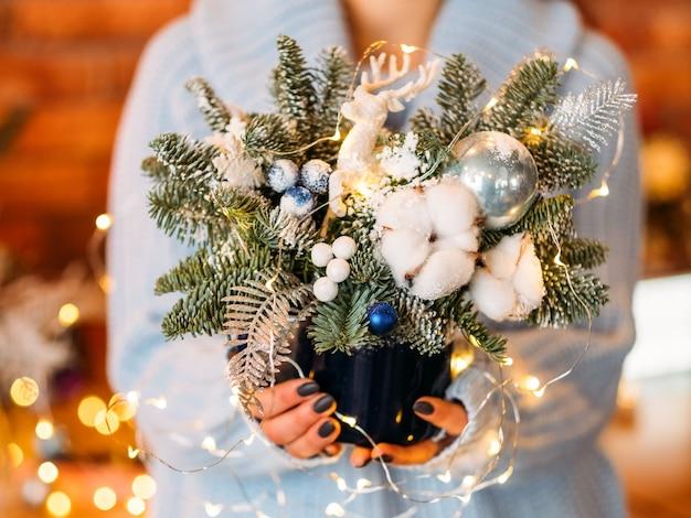 Handgemaakt kerstdecor. dame met pot met dennenboomtakjes en kerstverlichting.
