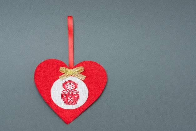 Handgemaakt rood speelgoed gemaakt van vilt in de vorm van een hart met een kruissteekmatryoshka met kopieerruimte